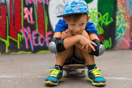hugging knees: Full Length Portrait of Young Boy Wearing Baseball Cap Sitting on Skateboard Hugging Knees and Smiling at Camera in front of Graffiti Covered Wall in Skate Park Stock Photo