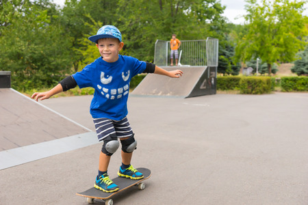 elbow pads: Young boy wearing protective knee and elbow pads and a trendy blue outfit riding his skateboard at a skate park enjoying his summer vacation