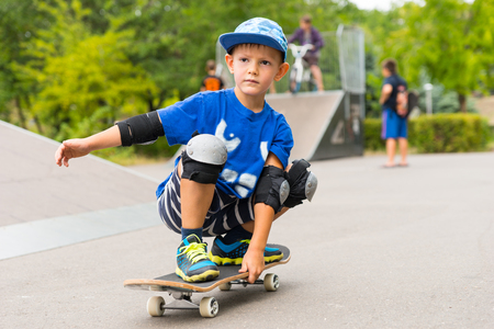 squatting down: Little boy practicing on his skateboard at a skate park squatting down with one arm extended for balance approaching close to the camera Stock Photo