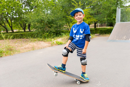 grins: Cute confident little boy posing on a skateboard at a skate park with one end lifted in the air as he grins at the camera Stock Photo