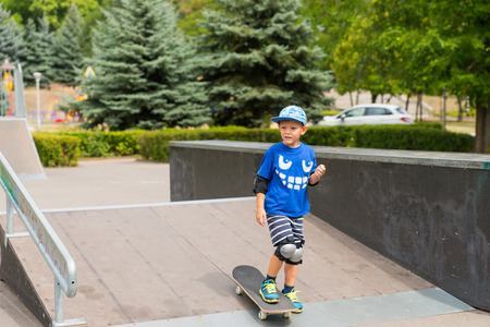 jaunty: Young boy skateboarding at the skate park standing on a shallow ramp looking around waiting for someone or watching something Stock Photo