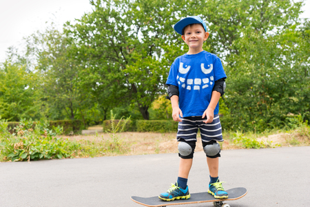 jaunty: Proud little boy with his new skateboard posing standing on it for the camera with a jaunty smile