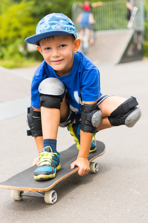 squatting down: Friendly sporty little boy with a lovely smile squatting down on his skateboard at a skate park in his knee and elbow pads for protection Stock Photo