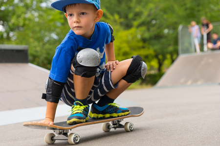 skaters: Full Length Close Up of Serious Young Boy Crouching on Skateboard in Skate Park with Other Skaters in Background on Ramp