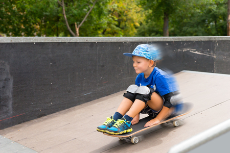 elbow pad: Little boy speeding down a ramp on a skateboard at the skate park smiling happily as he sits on the board in his trendy blue outfit, motion blur Stock Photo