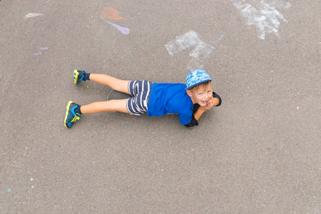 preteen boys: High Angle Full Length View of Young Boy Lying on Stomach on Skateboard in Concrete Parking Lot and Looking Up at Camera with Copy Space