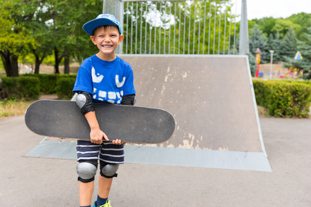 jaunty: Young boy posing with his skateboard at the park holding it under his arm as he gives the camera a beaming smile, ramp in the background Stock Photo