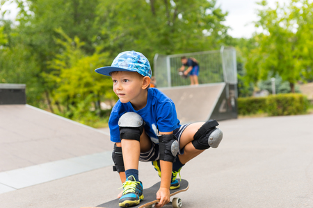 crouched: Full Length of Young Boy Riding Skateboard in Crouched Position in Skate Park with Ramp in Background - Looking Focused and Concentrating