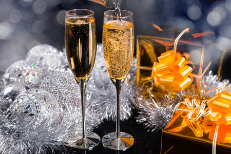 giftwrapped: Sparkling champagne for Christmas in two elegant flutes with silver decorations and golden gifts in a festive background Stock Photo