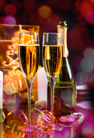 shiny background: Festive New Year Still Life - Two Glasses of Sparkling Champagne with Bottle, Pocket Watch and Gold Wrapped Gifts on Shiny Background Stock Photo