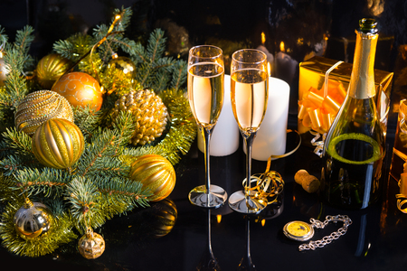 champagne: High Angle Festive Still Life - Two Glasses of Sparkling Champagne with Bottle, Candles, Gifts, Pocket Watch and Christmas Decorations on Black Background