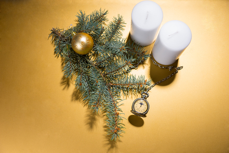 christian candle: High Angle View of White Pillar Candles on Golden Yellow Background with Evergreen Branch, Gold Ball and Antique Pocket Watch with Copy Space and Spot Lighting