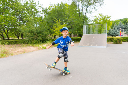 jaunty: Full Length of Determined Young Boy Wearing Safety Pads and Cap Doing Simple Trick on Skateboard in Skate Park on Summer Day Stock Photo