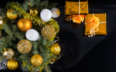 themed: Gold themed Christmas background with two decorative gifts, candles and an arrangement of baubles and pine branches, overhead view on black with copyspace