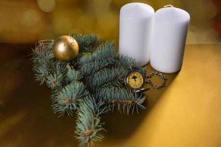 evergreen branch: Vista elevada de las velas del pilar blancas sobre fondo amarillo de oro con Evergreen Branch, Balón de Oro y el antiguo reloj de bolsillo con copia espacio y la iluminación del punto