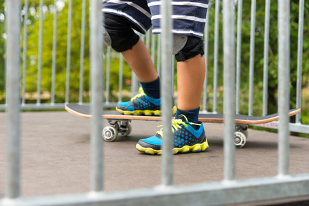 knee pads: Close Up of Young Boy Wearing Sneakers and Knee Pads and Striped Shorts with One Foot on Skateboard at Top of Ramp in Skate Park as seen through Bars of Guard Rail