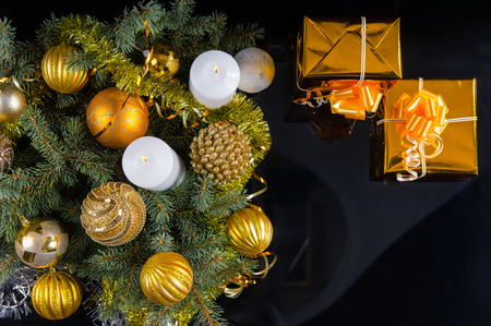 giftwrapped: Gold themed Christmas still life with baubles and ornaments on green pine branches surrounding two burning candles and two flutes of romantic champagne, overhead view on black Stock Photo