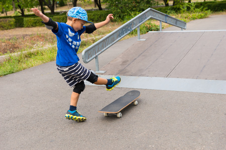 skater boy: Full Length of Enthusiastic Young Boy Kicking Foot Up at Skateboard at Bottom of Ramp in Skate Park on Summer Day Stock Photo