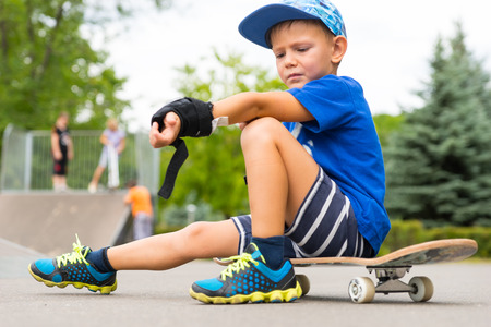 skater boy: Full Length of Young Boy Looking Upset Down at Arm While Adjusting Elbow Pad and Sitting on Skateboard in Skate Park on Summer Day