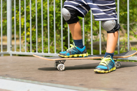 knee pads: Close Up of Young Boy Wearing Sneakers and Knee Pads and Striped Shorts with One Foot on Skateboard at Top of Ramp in Skate Park on Sunny Summer Day Stock Photo