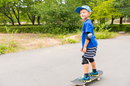 jaunty: Full Length Front View of Smiling Young Boy Wearing Summer Clothes Skateboarding with Eyes Closed in Paved Lot Surrounded by Lush Green Trees with Copy Space Stock Photo