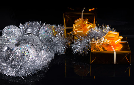 giftwrapped: Festive Christmas still life with silver decorations and tinsel and two luxury gold gifts decorated with bows on a dark background with copyspace