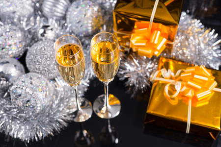 giftwrapped: Luxury Christmas still life with two flutes of sparkling champagne, decorated gold gifts and an arrangement of silver tinsel and Xmas decorations viewed high angle on a black background