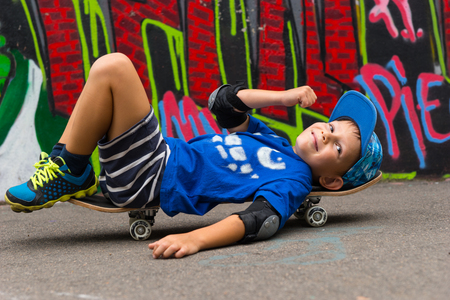 elbow pads: Full Length Profile of Young Boy Wearing Elbow Pads Lying on Back on Skateboard with Raised Fist and Smiling at Camera in Paved Lot in front of Graffiti Covered Wall