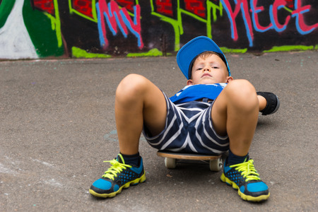 young boy smiling: Full Length of Serious Young Boy Wearing Summer Clothes Lying on Back on Skateboard and Looking Down Toward Raised Knees in Paved Lot in front of Graffiti Covered Wall Stock Photo