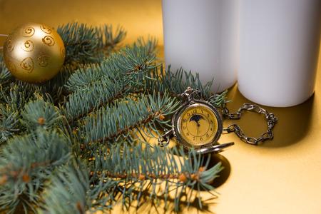 evergreen branch: Primer plano festivo Todav�a vida de reloj de bolsillo antiguo rodeado de velas Pilar Blanco y Evergreen Branch decorado con Sola bola de la Navidad del oro sobre fondo amarillo