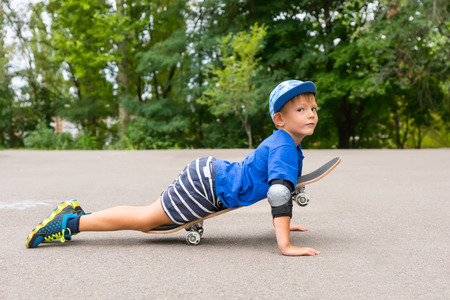 preteen boy: Full Length Profile of Young Boy Lying on Skateboard and Propping Self Up on Arms While Looking at Camera in Parking Lot Surrounded by Lush Green Trees Stock Photo