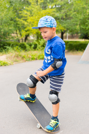 preteen boys: Full Length of Determined Young Boy Wearing Safety Pads and Cap Doing Simple Trick on Skateboard in Skate Park on Summer Day Stock Photo