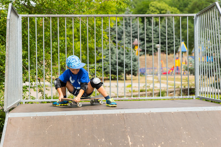 knee pads: Young Boy Wearing Knee Pads Straddling Skateboard on Top of Ramp in Skate Park, Sitting on Skateboard as if Gathering Courage to Ride Down Stock Photo