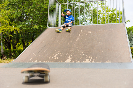 skate park: Young Boy Sitting on Top of Ramp in Skate Park with Skateboard in Foreground at Bottom of Ramp in Soft Focus, Outdoors on Sunny Day