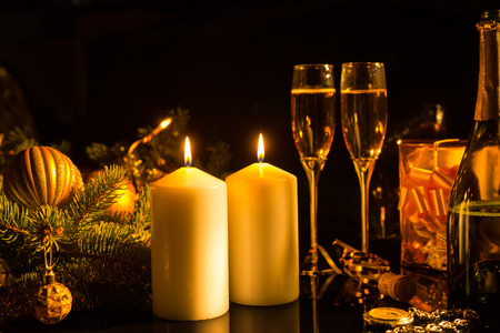 sentimental: Romantic Still Life of Lit Candles Illuminating Glasses of Champagne on Dark Background with Christmas Decorations and Gifts - Sentimental Image of Festive Burning Candles in Warm Light Stock Photo