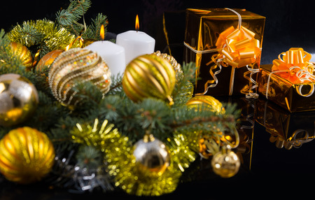 themed: Colorful gold themed Christmas still life with baubles nestling in pine branches alongside two elegant gifts in gold foil with bows, dark background with copyspace