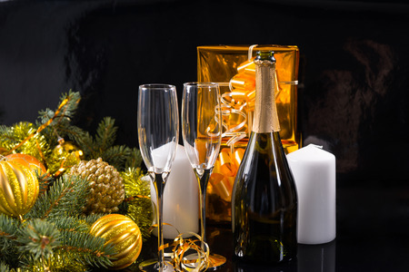 champagne: Festive Still Life of Bottle of Champagne with Elegant Glasses on Black Background with White Candles, Gold Wrapped Gifts and Evergreen Branches Decorated with Gold Christmas Balls and Tinsel Stock Photo