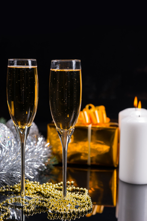 string of pearls: Festive Christmas Still Life with Copy Space - Golden String of Pearls on Glossy Black Table with Glasses of Champagne, Gold Wrapped Gifts, Lit Candles and Silver Decorations
