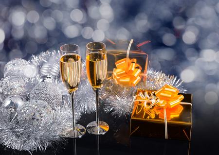 giftwrapped: Festive Christmas Still Life with Copy Space - Pair of Champagne Glasses in Glittering Still Life with Gold Wrapped Presents, Silver Tinsel Garland and Decorative Ornaments Stock Photo