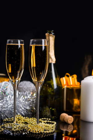 new year eve beads: Festive Christmas Still Life - Two Glasses of Sparkling Champagne with String of Gold Beads, Bottle of Champagne and Decorations in front of Black Background