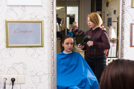 blow dryer: Reflection in Mirror of Young Brunette Woman Having Wet Hair Dried by Blond Stylist Using Hot Air Blow Dryer in Salon, Framed by Certificate of Education Credentials Hanging on Wall Stock Photo