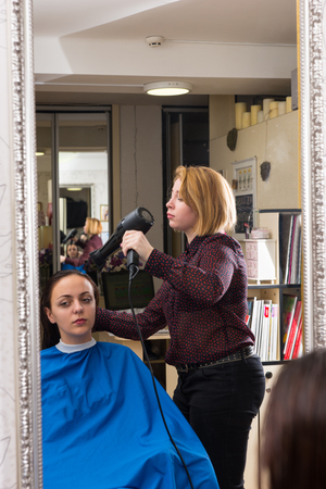 smock: Reflection in Mirror of Blond Stylist Using Blow Dryer to Dry Hair of Female Brunette Client Wearing Smock and Seated in Chair in Salon