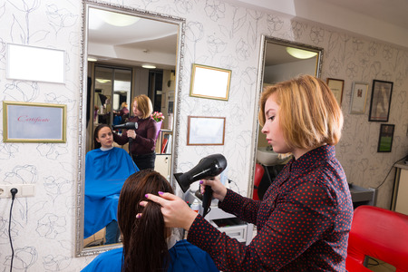 blow dryer: Profile of Young Blond Stylist Drying Hair of Female Brunette Client Using Blow Dryer in Salon with Reflection in Mirror in Background