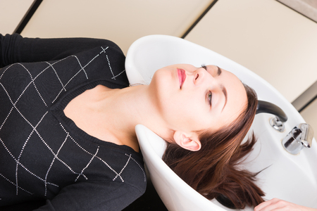 lying on back: Close Up of Brunette Woman Lying Back with Head Resting in Hair Wash Sink, Looking Relaxed and Contented, in Salon Spa