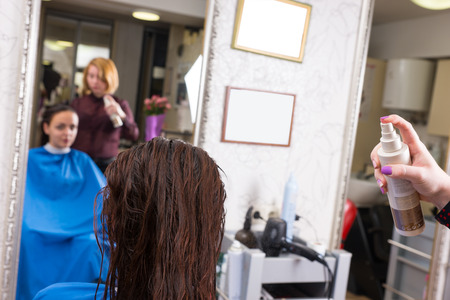 atomiser: Close Up Rear View of Stylist Spraying Product onto Wet Hair of Brunette Female Client Seated in Salon Chair with Blurred Mirror Reflection in Background Stock Photo