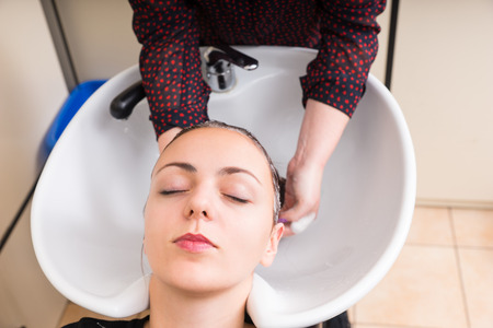lying on back: High Angle Close Up View of Young Brunette Woman Lying Back with Eyes Closed and Having Hair Washed by Stylist in Salon Sink - Woman Relaxing While Having Hair Washed Stock Photo