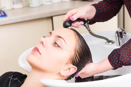 Close-up profiel van de jonge donkerbruine vrouw die Haar Gewassen en gespoeld door Stylist in Sink in Salon Spa Stockfoto