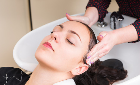 rinsing: Close Up of Young Brunette Woman Lying Back with Eyes Closed and Having Hair Washed by Stylist in Salon Sink - Woman Relaxing While Having Hair Washed Stock Photo