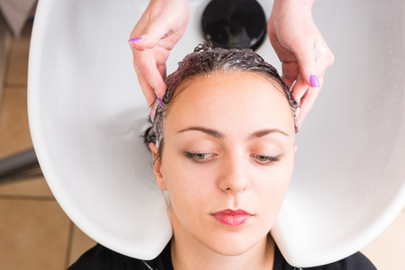 eyes looking down: High Angle Close Up View of Young Brunette Woman Having Hair Washed by Stylist in Sink in Salon Spa, Woman with Relaxed Eyes Looking Down and to the Side
