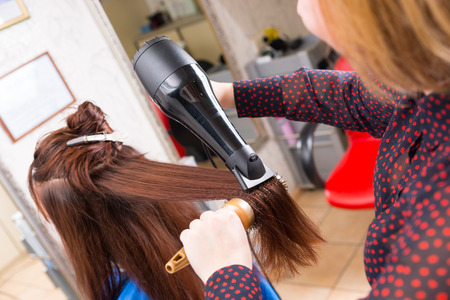 blow dryer: Close Up Rear View of Young Blond Stylist Drying Hair of Brunette Client Using Handheld Blow Dryer and Round Brush in Salon